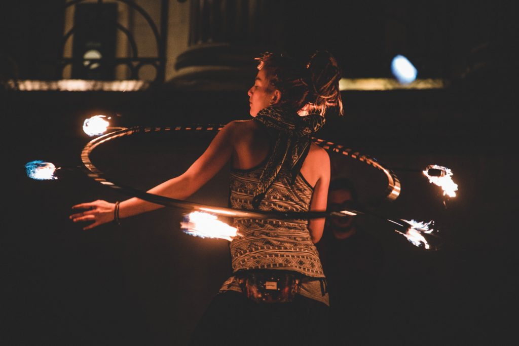 Woman juggling fire with hula-hoop